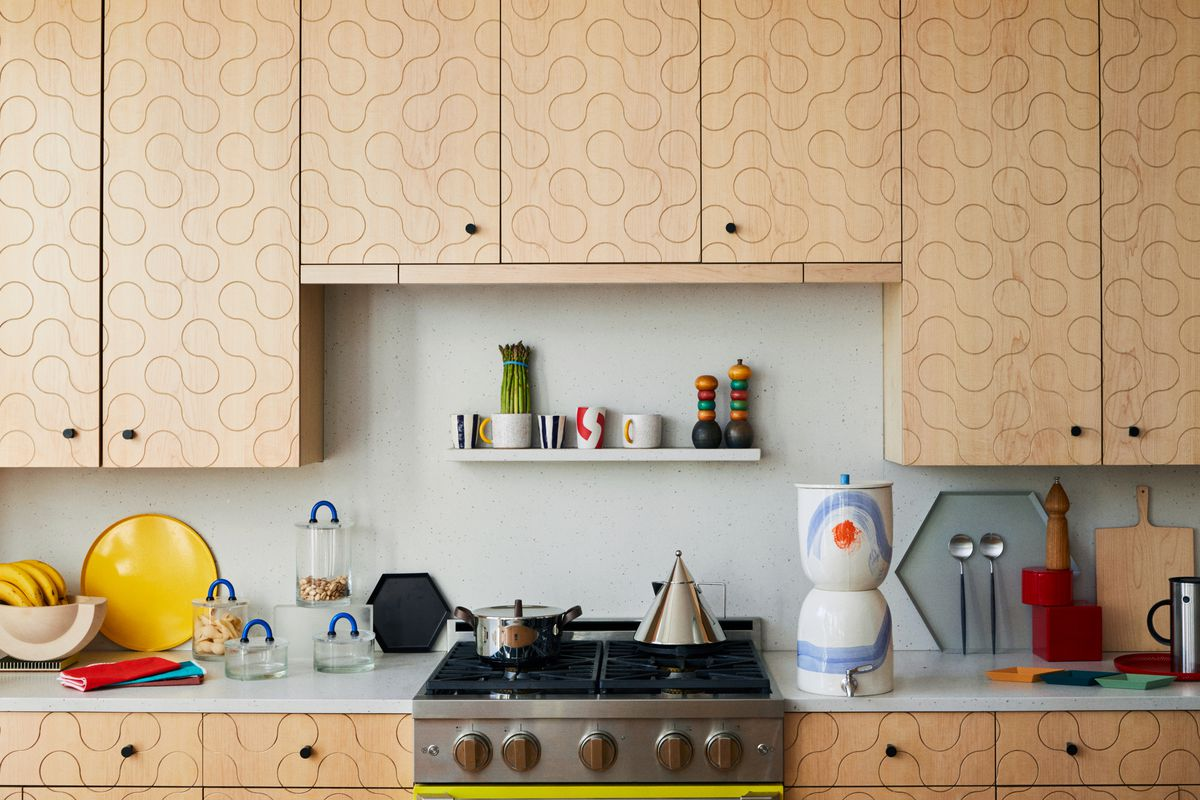 A kitchen countertop is filled with various plates, pots, water containers, and cutlery. The kitchen also has wooden cabinets with a squiggle pattern.