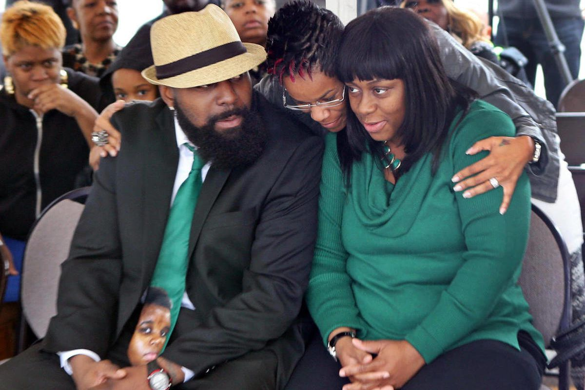 Michael Brown Sr., left, and his wife, Calvina Brown, right, are embraced by Trina Moorehead, of Florissant, upon their arrival at the Flood Christian Church service that was held in a tent on Sunday, Nov. 30, 2014, in Country Club Hills, Mo. The church w