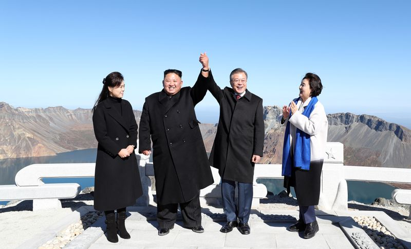 Kim and Moon raise their held hands aloft in celebration alongside their wives.