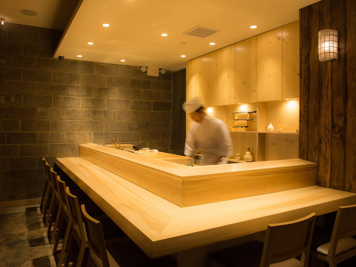 Sushi Amane's sushi bar counter has yellow wood, with a chef wearing white standing in the middle