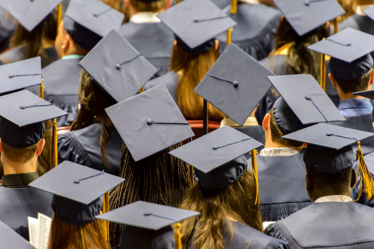 Students wear caps and gowns at their graduation.