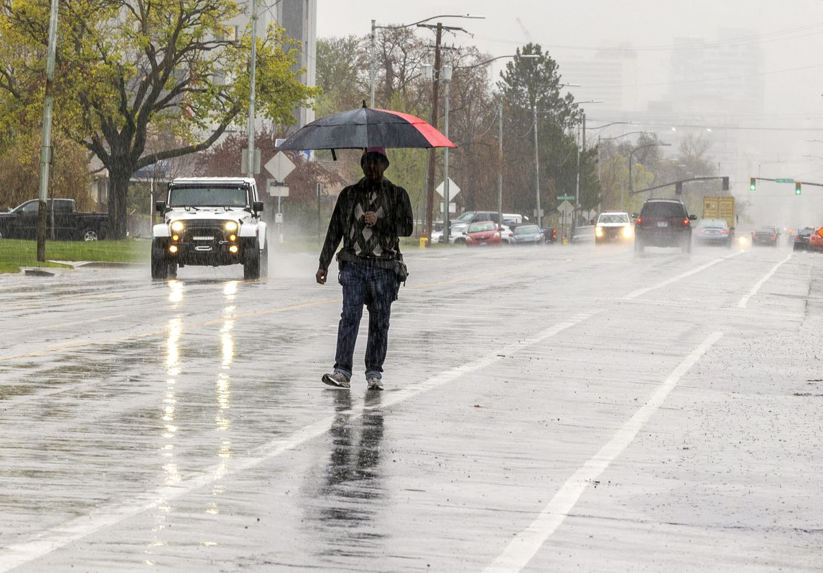 A man with an umbrella walks in the rain along Main Street and about 2100 South in Salt Lake City on Monday, April 26, 2021.
