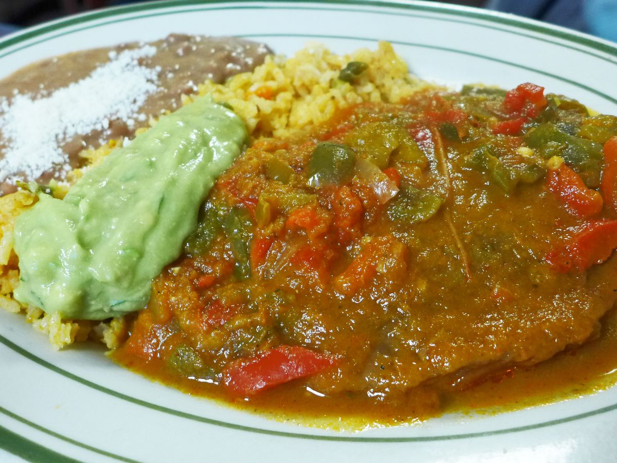 A cheese stuff chile flooded with tomato sauce, alongside rice and beans.