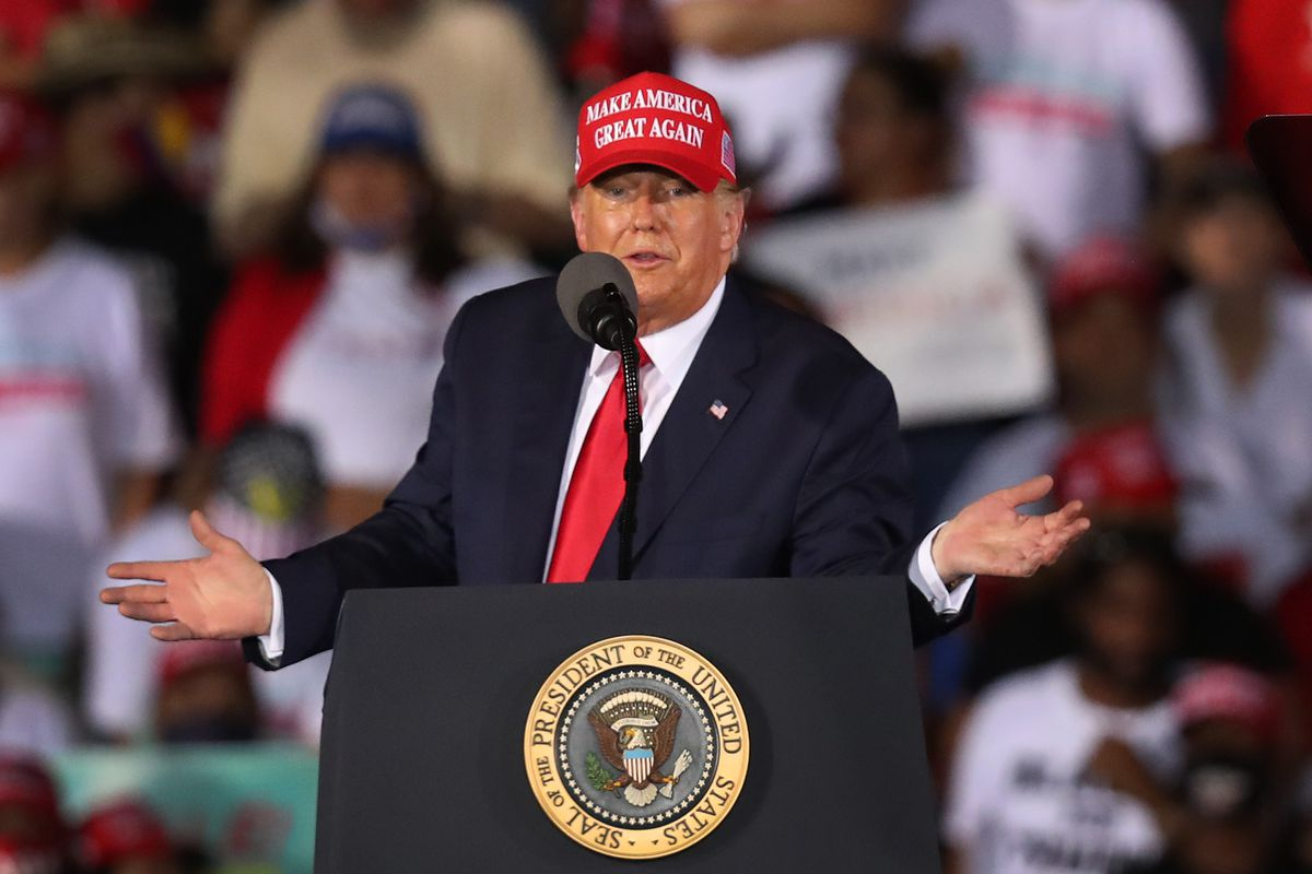 President Donald Trump gesturing from behind a podium and wearing a MAGA hat.