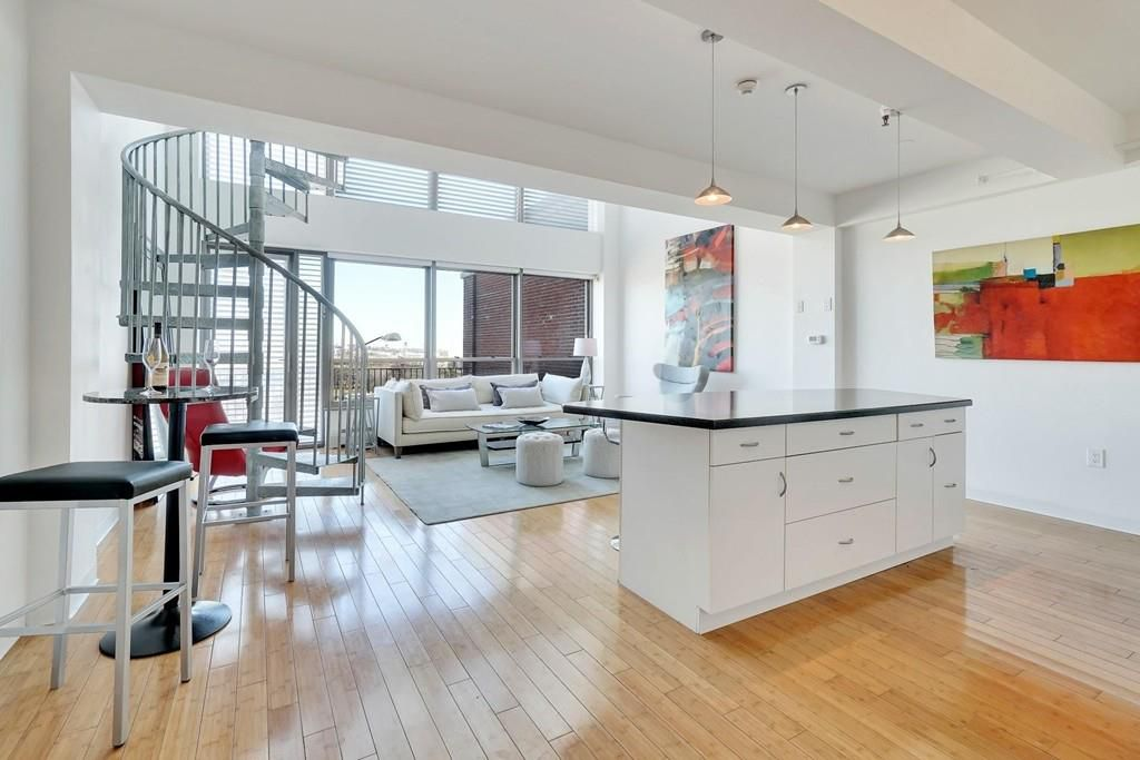 An open kitchen-living room with a view over the kitchen island, and to the left of that is a spiral staircase.