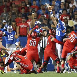 Utah Utes place-kicker Matt Gay (97) kicks a field goal over the Brigham Young Cougars defense in Provo on Saturday, Sept. 9, 2017.