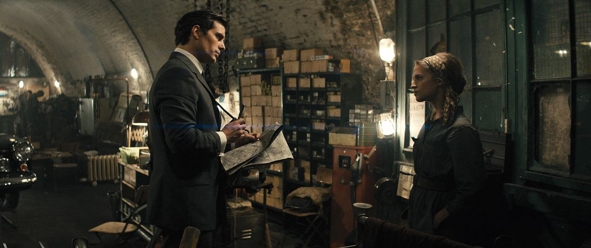 A dapper Henry Cavill confronts a grubby Alicia Vikander in a cluttered safehouse in The Man From UNCLE.