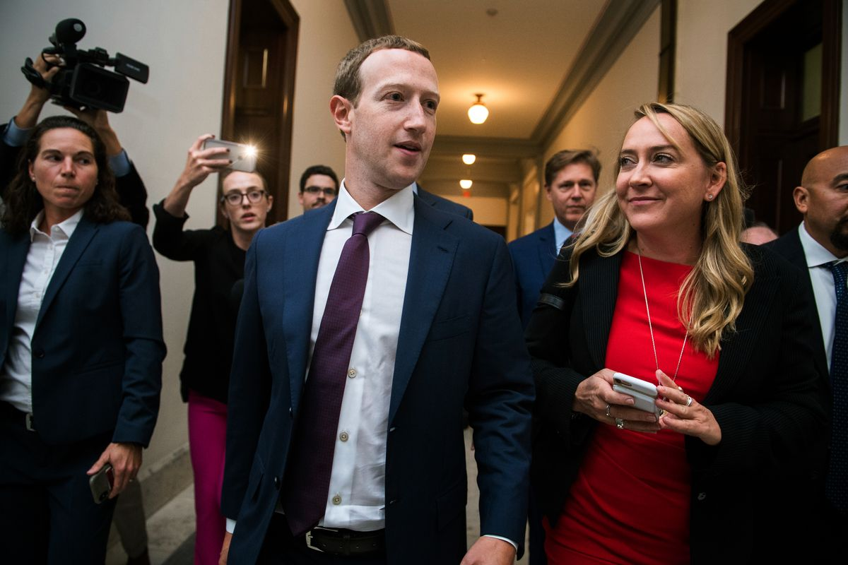 Facebook CEO Mark Zuckerberg walking down a hall on Capitol Hill flanked by reporters.