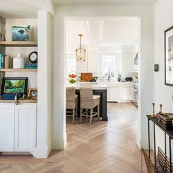 The first-floor redesign created long sight lines and clear traffic flow. This view from the front entry into the kitchen, past a storage nook in the living room, illustrates this feeling of space.