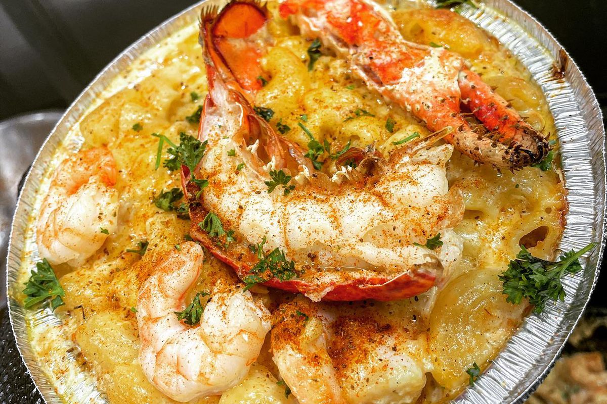 A cheesy takeout dish is stacked with a lobster tail, shrimp, and a snow crab claw