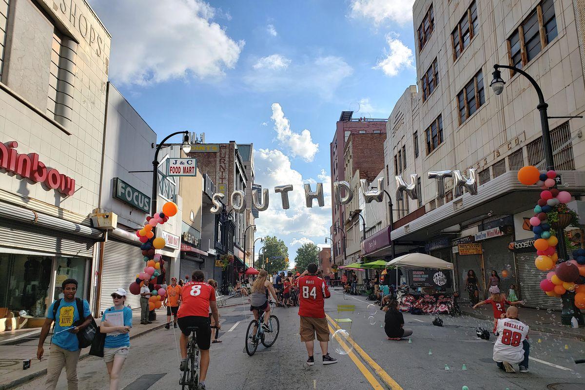 Pedestrians walking and biking down Peachtree Street in downtown Atlanta.