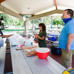 Paul Chavez, left, puts the food on the table while talking to Katrina Dobieski and Kevin McDowell at Liberty Park in Salt Lake City on Monday, Aug. 17, 2020.