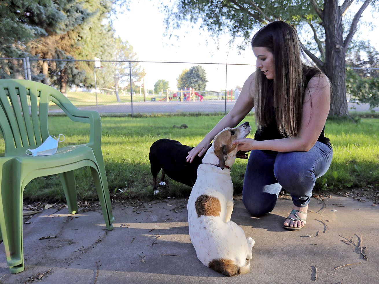 Lisa O'Brien plays with her dogs Jersey and Dottie outside of her home in Roy on Monday, Aug. 17, 2020. O'Brien has suffered blood clots, tachycardia and excessive fatigue in the five months since she was sick in early March with what she and her doctors believe was COVID-19.