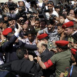 CORRECTS DAY AND DATE - Former Egyptian Vice President Omar Suleiman, center, is escorted by military police as he prepares to submit his candidacy papers at the Higher Presidential Elections Commission, in Cairo, Egypt, Sunday, April 8, 2012. A former strongman of ousted President Hosni Mubarak's regime has announced his presidential candidacy, shaking up an already heated race that is emerging as a contest between two longtime rivals _ former regime officials and Islamists who have surged in influence. (AP Photo/Amr Nabil)