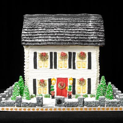 Gingerbread house with white icing exterior and windows with wreaths and black shutters.