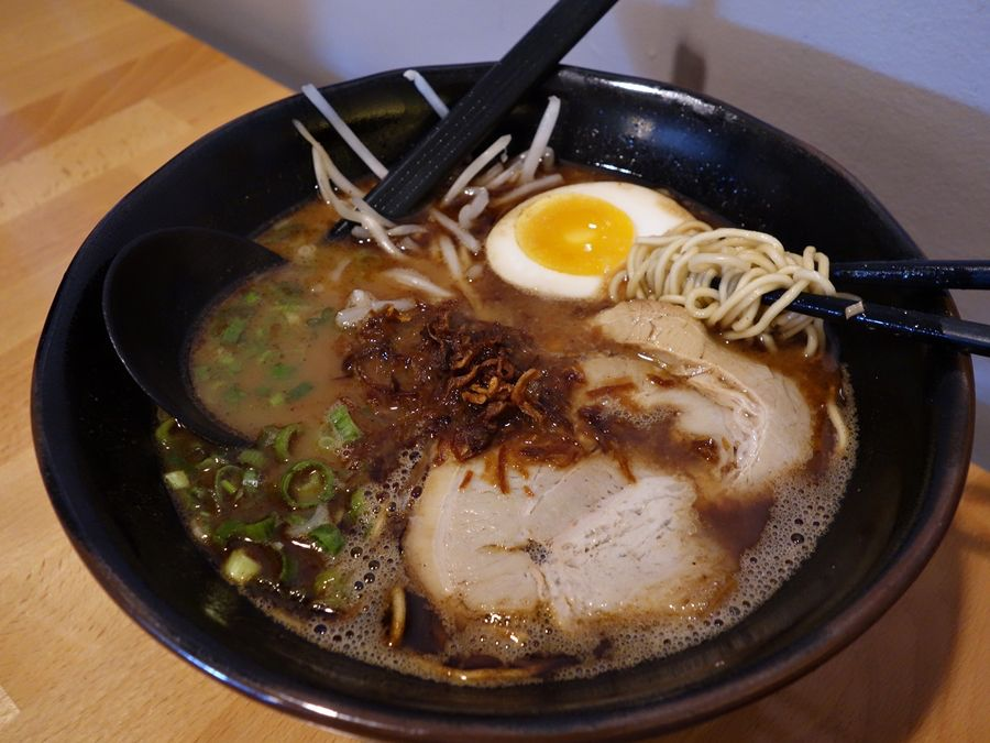 A black bowl filled with black ramen, topped with pork and and egg.