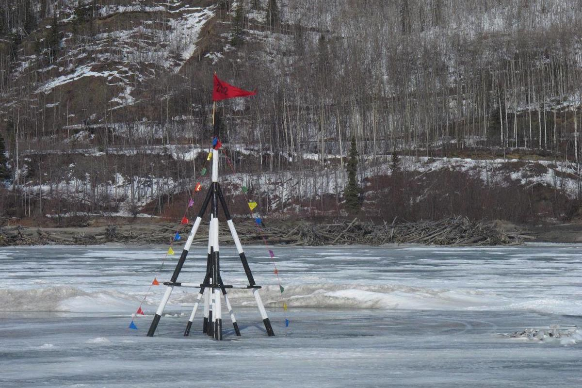 FILE - In this Thursday, April 12, 2012 file photo, a red flag is whipped by wind on a tripod sitting on the frozen Nenana River on, in Nenana, Alaska. The tripod serves as the basis for Alaska's biggest guessing game, with people buying tickets to guess