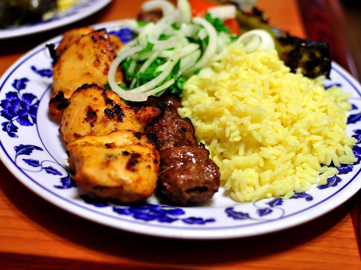 A plate of grilled kebabs and yellow rice at Elena's Greek Armenian Cuisine.