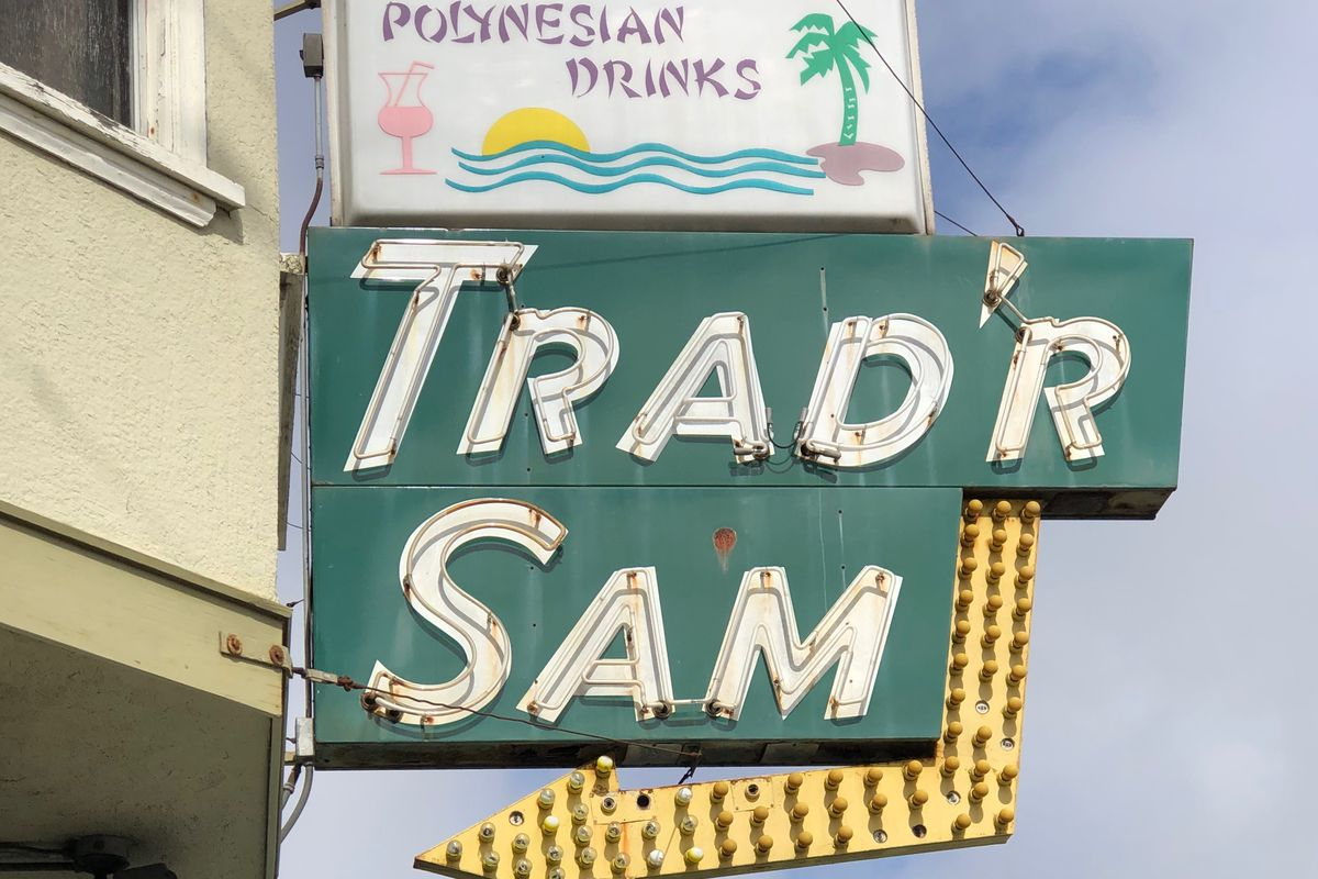 Trad'r Sam's Neon sign and arrow above the bar's exterior