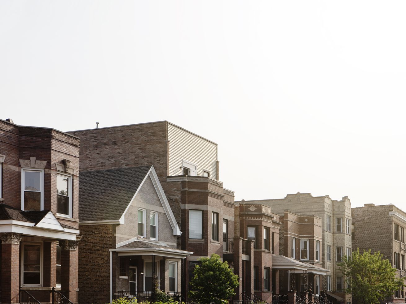 A view of brick two-story homes, workers cottages, and old Chicago craftsman houses with a white sky.