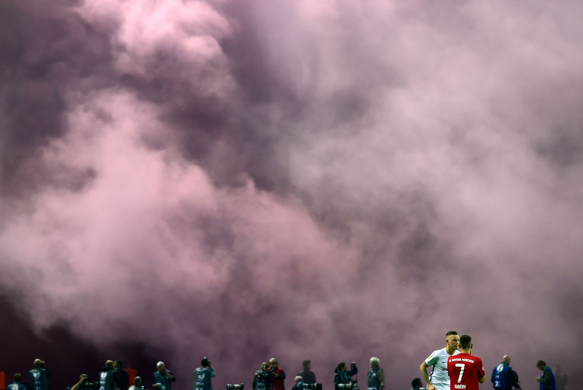 Bayern Munich's French midfielder Franck Ribery waits as smoke rises as fans light flares ahead the second half time of the German Cup DFB Pokal final football match FC Bayern Munich vs Eintracht Frankfurt at the Olympic Stadium in Berlin on May 19, 2018.
