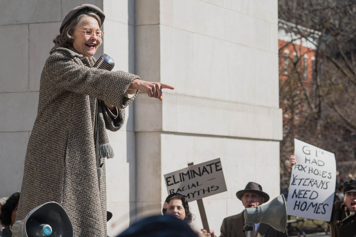 """A gray-haired woman in a wool coat and orange glasses stands in front of a white stone structure. People hold hand-written signs in the background reading """"Eliminate racial myths"""" and """"GI had fox holes veterans need homes."""""""