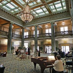 A woman plays the piano while others sit and relax or walk around the lobby of the Joseph Smith Memorial Building.