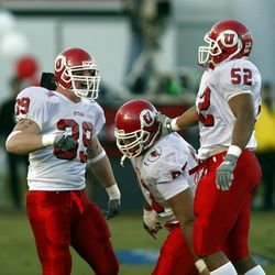 Defensive players Zach Tune, Jason Kaufusi and Marcus Jones celebrate in the fourth quarter as  Utah beat USC 10-7 in the Las Vegas Bowl on Dec. 25, 2001. Photo by Tom Smart