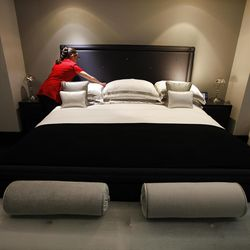 This  Friday, March, 16, 2012 photo shows a maid adjusting the pillows in one of the five bedroom  luxury penthouse apartments overlooking Hyde Park, London.