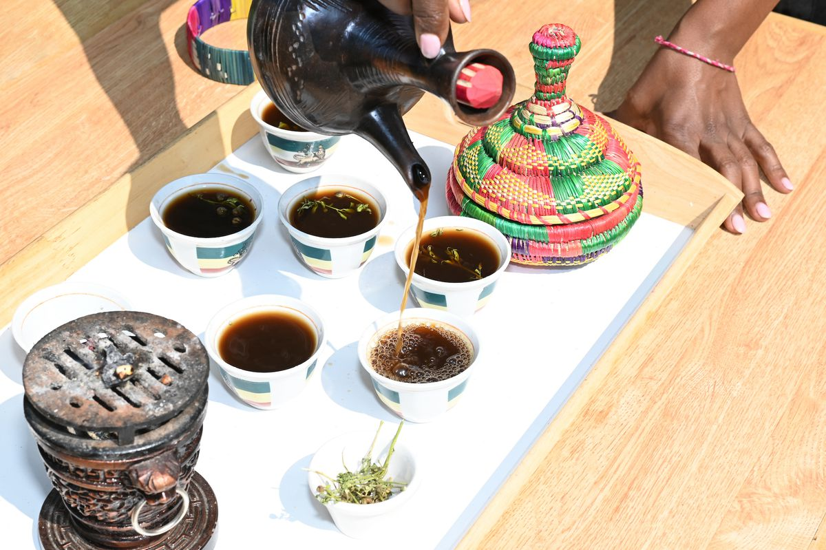 An overhead, well lit shot of a hand pouring coffee from a mug in a traditional coffee ceremony.