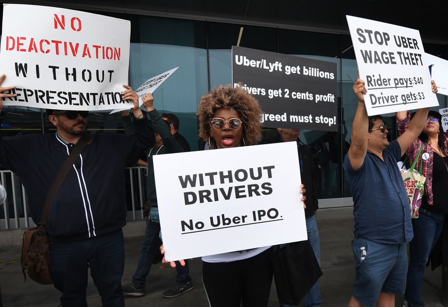 "Uber and Lyft drivers strike at LAX International Airport. One woman holds a sign that says, ""Without drivers, no Uber IPO."""