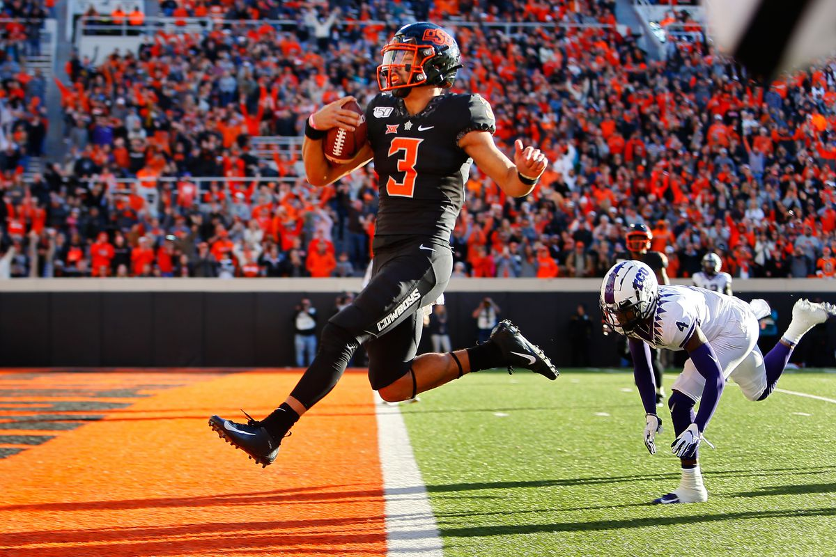 Quarterback Spencer Sanders of the Oklahoma State Cowboys leaps into the end zone for a 43-yard touchdown against safety Keenan Reed of the TCU Horned Frogs only to have it called back for an illegal shift in the fourth quarter on November 2, 2019 at Boone Pickens Stadium in Stillwater, Oklahoma.