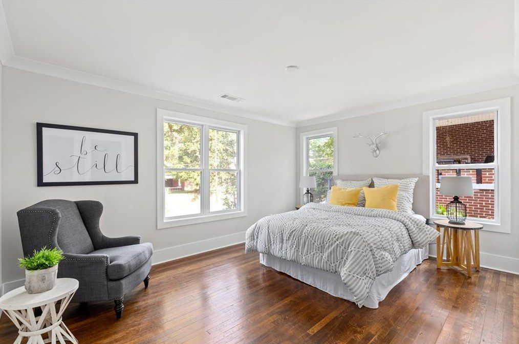 A white bedroom with four windows.
