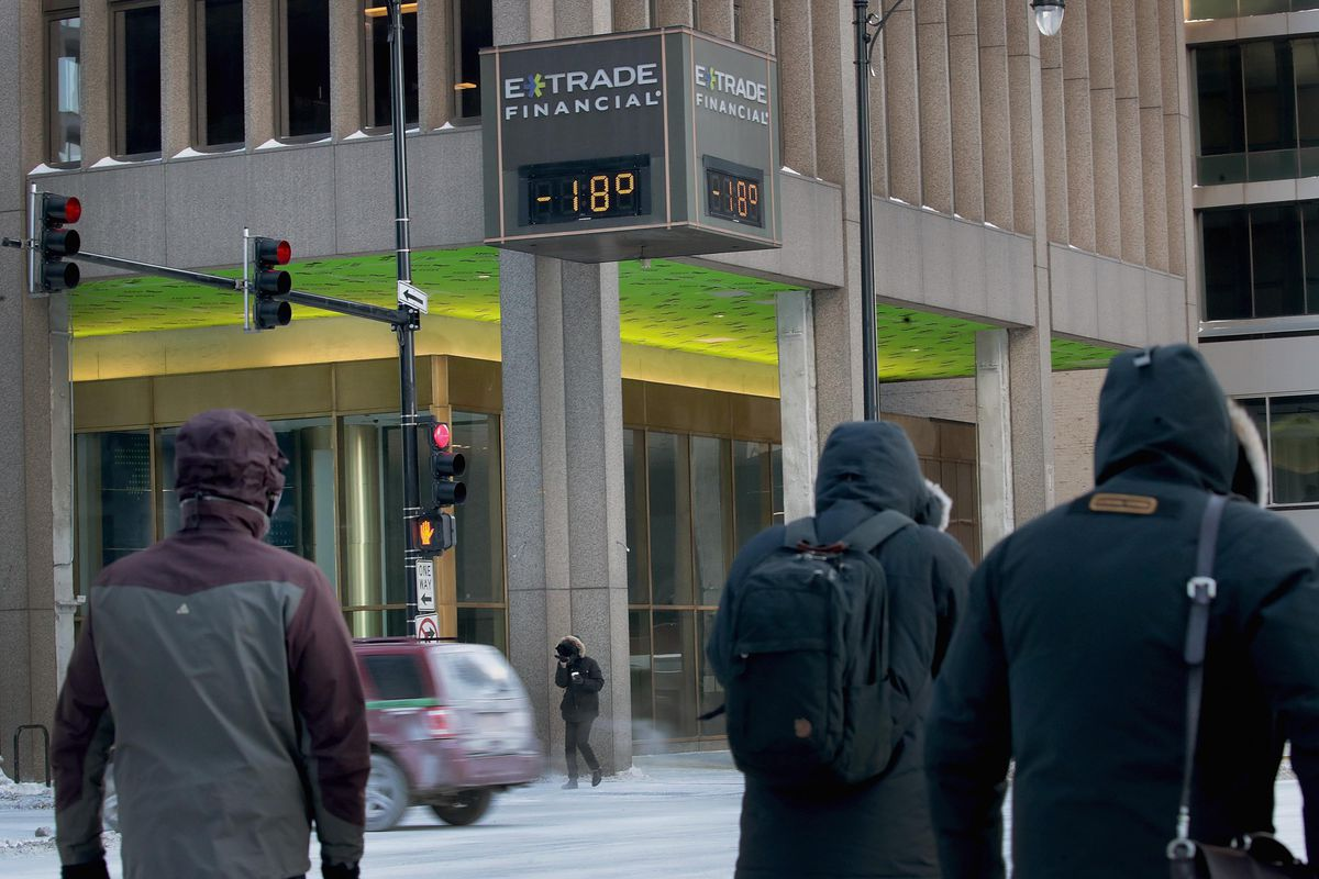 """Commuters in downtown Chicago on January 31, 2019, walk past a sign that reads """"E-Trade Financial: -18 degrees."""""""