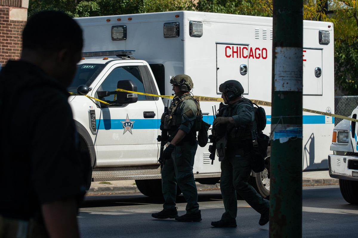 Members of a SWAT team walk along West Division Street near the 1200 block of North Mason Avenue in the Austin neighborhood, where a person was fatally shot and two were injured Friday morning.