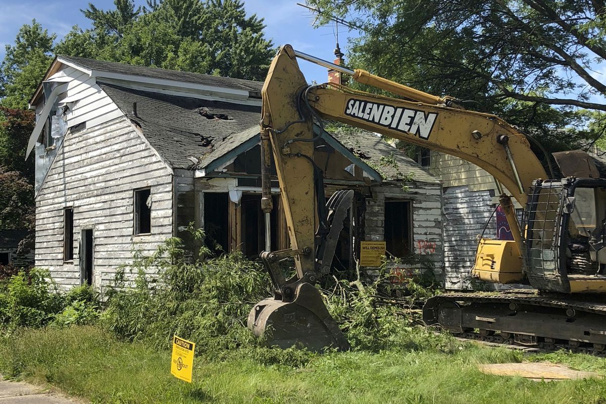 An abandoned, windowless home with white wood siding. A yellow excavator sits next to it.
