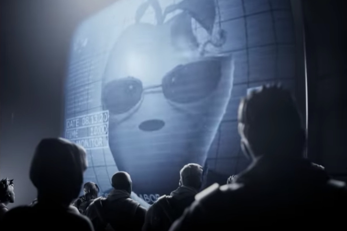 An imposing figure with a giant apple for a head and sunglasses speaks to a subservient audience over a TV monitor