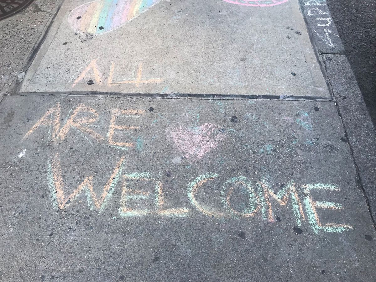 """A message written in chalk on a sidewalk that reads: """"All are welcome."""""""