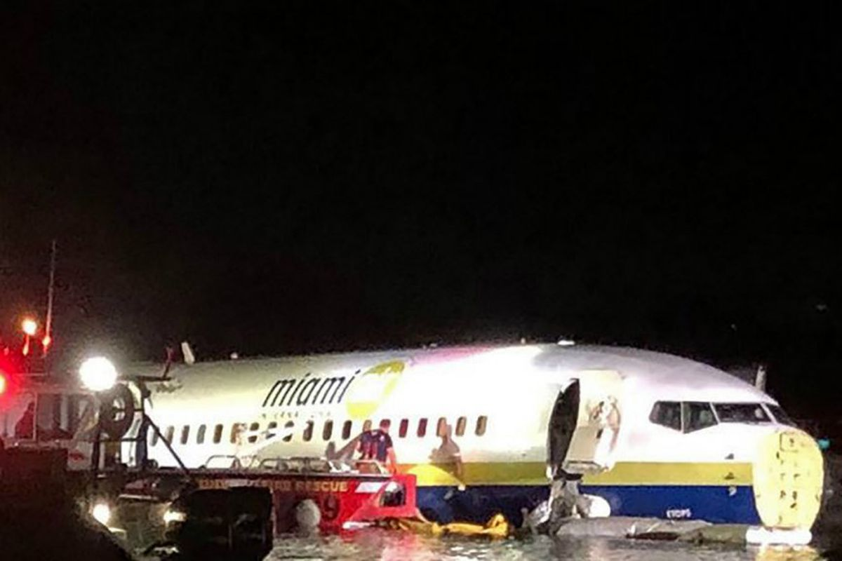 A Miami Air International partially submerged in a river in Jacksonville; emergency response teams work to evacuate passengers.