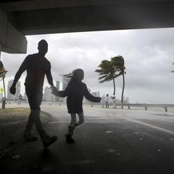 The winds and sea are whipped up off of the Rickenbacker Causeway as two people cross the street in Miami as Hurricane Irma approaches on Saturday, Sept. 9, 2017.