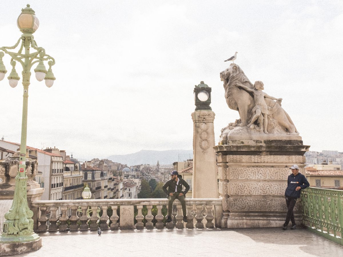 A man sits on a railing over Marseilles, France