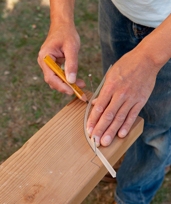 Man Draws Tail Profile Of Arbor Bench