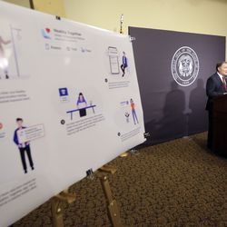 Gov. Gary Herbert speaks during the daily COVID-19 media briefing at the Capitol in Salt Lake City on Wednesday, April 22, 2020. A poster displaying how the Healthy Together app will use location tracking for COVID-19 contact tracing is on display in the foreground.