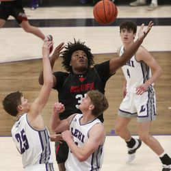 Bountiful's Rob Whaley grabs a rebound over the Lehi defense during a game at Lehi High School on Friday, Dec. 11, 2020.