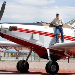 Andy Taylor, Owner of New Frontier Aviation poses on his plane Monday, July  16, 2012 as he talks about the job they do of fighting fires from the air.
