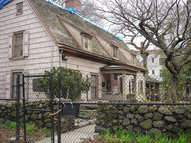 The exterior of a historic old house. There is weathered white siding on the facade and a green roof. There is a stone fence outside of the house.