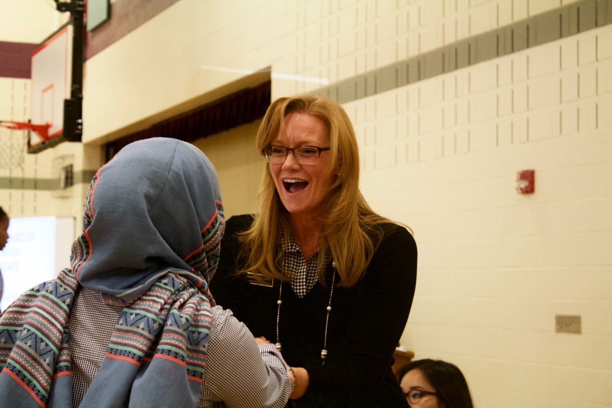 Rebecca McClellan, a candidate for the State Board of Education, greets a participant at a forum in Aurora.