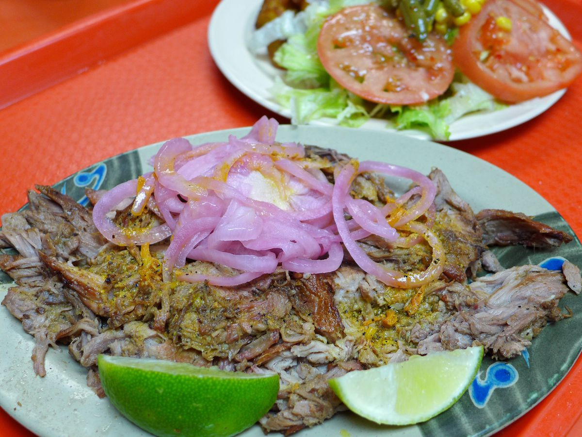 Wedges of lime sit next to a plate of roast pork topped with pickled onions.