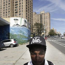 """Jerome Stewart, 15, wears a Brooklyn Nets cap as he walks home from school past the Ebbets Field Apartments, home of the former Brooklyn Dodgers, on Wednesday, Sept. 19, 2012 in Brooklyn, N.Y.  """"I used to be a Knicks fan"""" said Stewart, """"but switched to the Nets.""""  After decades without a professional sports team after the Dodgers moved west, Brooklyn is hitting the major leagues again with a new arena and the Brooklyn Nets' basketball franchise."""