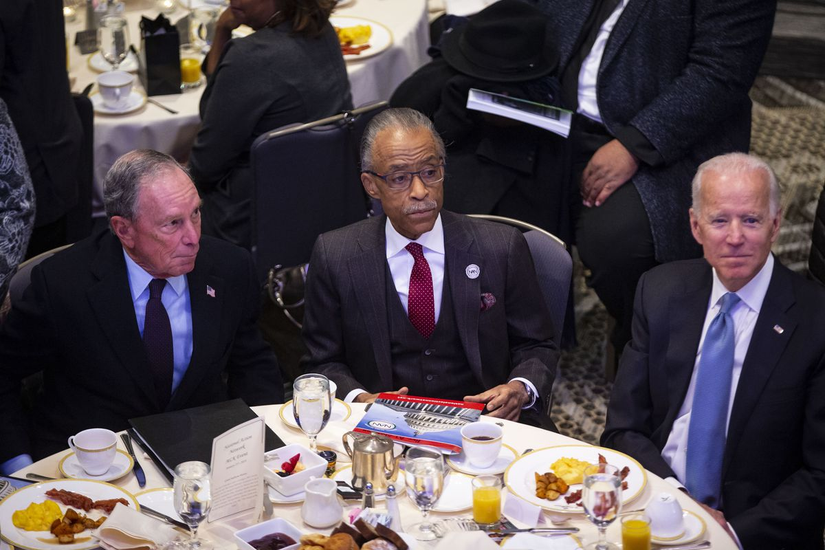 Mike Bloomberg sits at a breakfast table with Al Sharpton and Joe BIden.